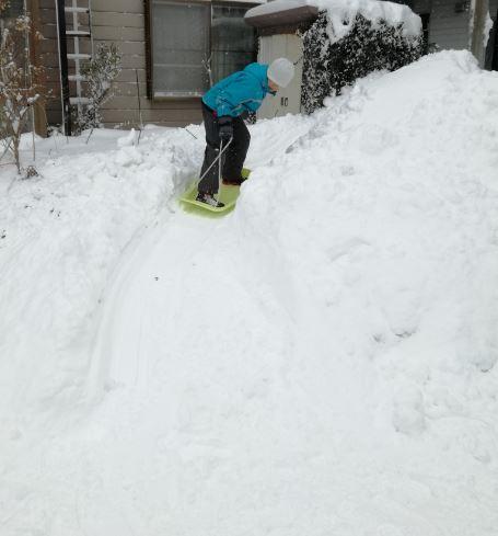 家の前の雪山でそり滑り