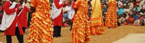 Hira Gasy sångare i gula och röda klänningar