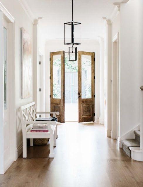 Белая прихожая и большие деревянные входные двери