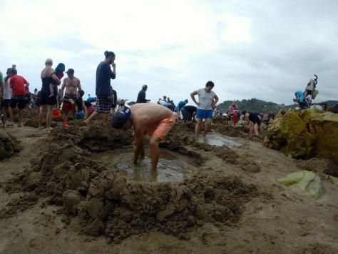 Digging a hole at Hot Water Beach in Coromandel, New Zealand via ZaagiTravel.com