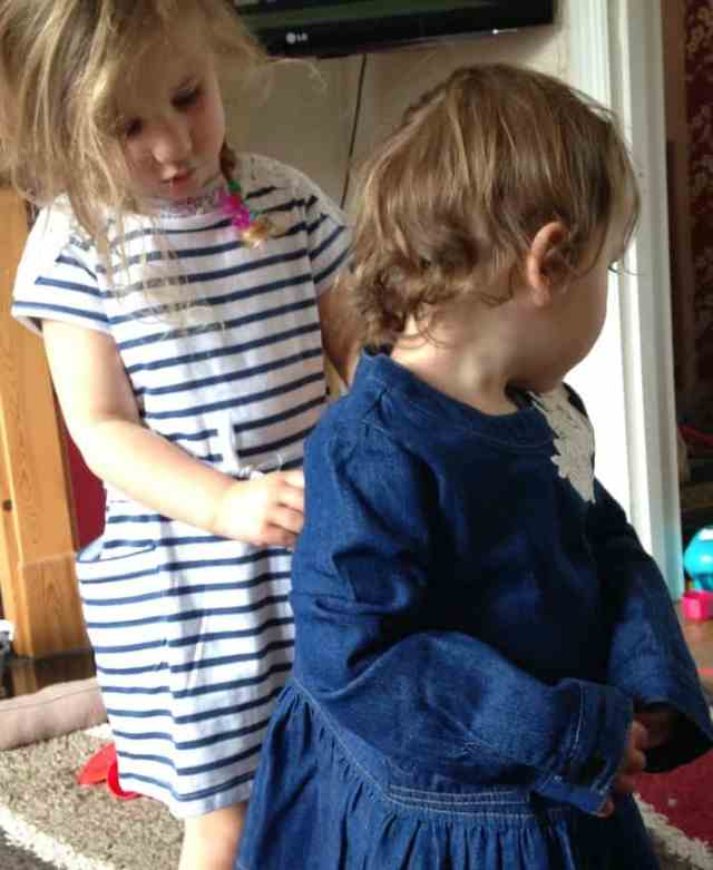 sister helping with dress