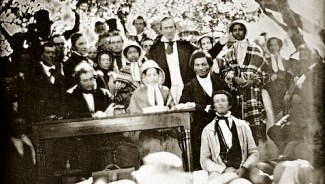 The 1850 Fugitive Slave Law Convention, Cazenovia, New York. The Edmonson sisters are standing wearing bonnets and shawls in the row behind the seated speakers. Frederick Douglass is seated, with Gerritt Smith standing behind him, and with Abby Kelley Foster the likely person seated on Douglass's left. Image: WikiCommons.