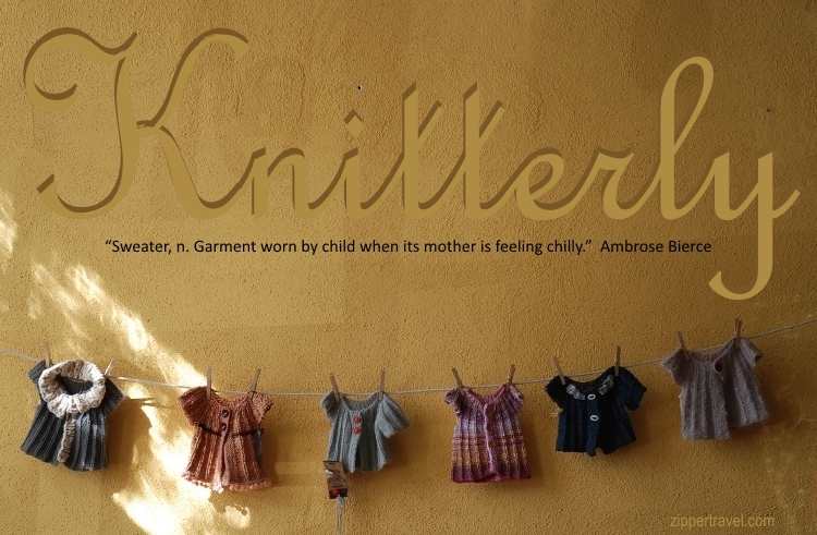 Baby sweaters hanging on a line with clothes pins at Knitterly in Petaluma California