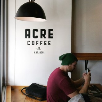 Man looking at his cell phone at Acre Coffee in Petaluma California