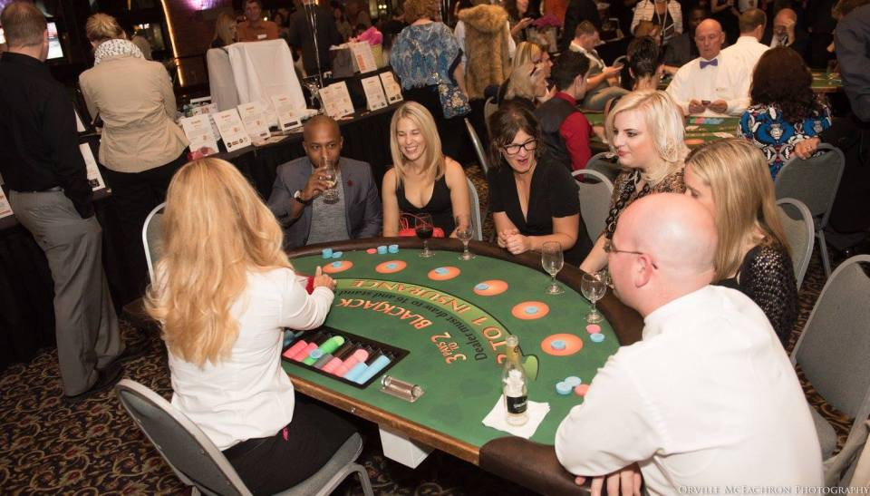 A group of people around a blackjack table.