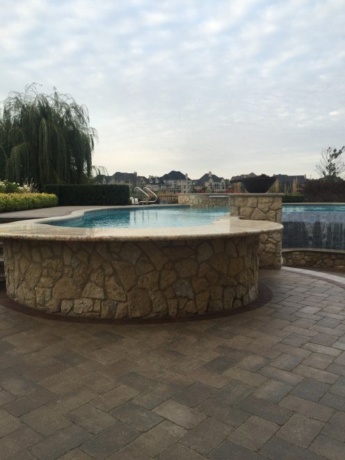 Curved Stone Wall with Pool Area