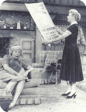 "Lucy Ricardo reads a poster to Ethel Mertz in ""Westport."" It says: ""Yankee Doodle Day Celebration -- Statue Dedication at Jessup (sic) Green."""