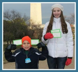 Nick and Nicole Mathias, with inauguration tickets.  The Washington Monument is in the background.