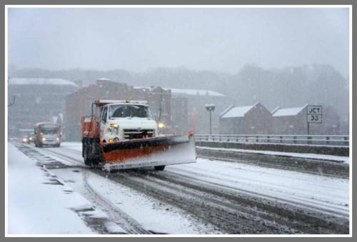 A plow crosses the Post Road bridge, early in Friday's blizzard. (Photo by Paul Schott/Westport News)