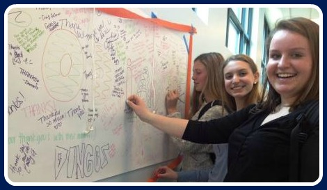 Staples students sign a large poster, thanking their custodians.