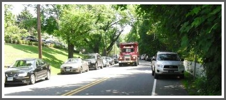A truck navigates through cars parked on both sides of South Morningside Drive...