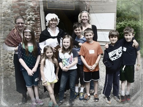 Third graders and parent docent volunteers stand happily outside the Wheeler barn.