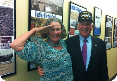 "Rindy Higgins salutes First Selectman Jim Marpe. He's wearing a ""USS Saugatuck"" cap, which she presented to him."