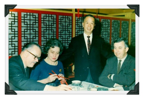 Eddie Lee with customers. A brave woman gingerly tries chopsticks.