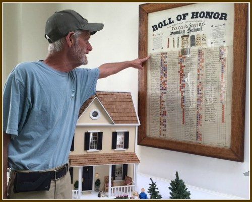 """Bob Custer points out some famous names -- Jennings, Sherwood, Wakeman, Rippe, Adams -- on a """"Wall of Honor."""" Those on the list are cited for their  Sunday school attendance from 1909 to 1916."""