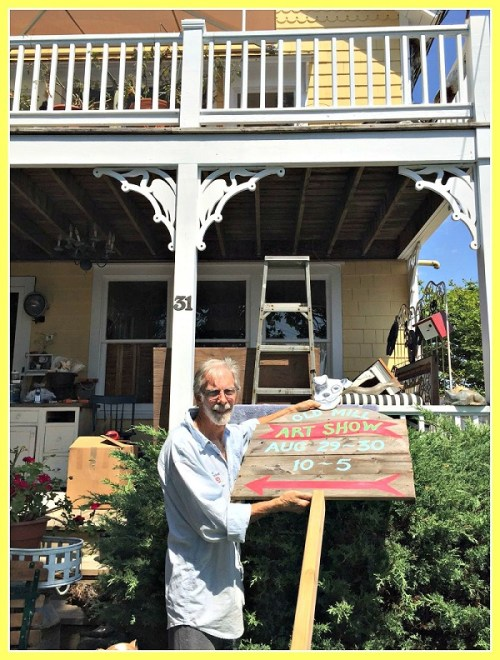 Clark Hanford advertises his art show, in front of his gingerbread-style house.