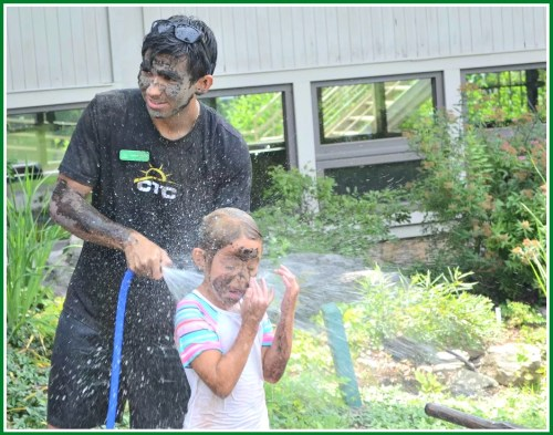 Jaime Bairaktaris at Earthplace's summer camp. He says it's a tossup which activity the kids like more: mud fights, or hosing off afterward. (Photo/Harris Falk)