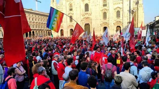 folla ad una manifestazione con bandiere varie