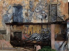 """Leslie writes: """"Oil – not tourism – is the main industry in Curacao (...) A second scene [of a larger mural] depicts a tiger ('Cha Tiger') taking off his Shell glasses ('blinders') flanked by goats, a giant spider ('Kompa Nanzi'), a woman and the Curacao flag. While I can only guess at the significance of these details, it's clear this artwork deals with the political, social and environmental impact of the oil industry."""" (This mural was created by Instituto Buena Bista guest artist Liesbeth Labeur with the assistance of IBB students. A Dutch artist, Labeur spent her childhood in Curacao and is writing a graphic novel about the """"waning days of the Shell corporation"""" on the island)"""