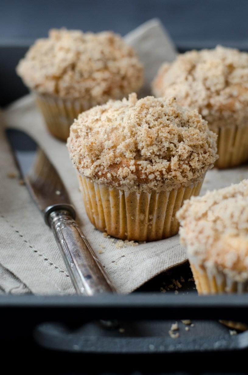 Skořicové muffiny s jablky si zamilujete! Jde o muffiny se skořicí s náplní z jablek povařených s Calvadosem a kardamomem, posypané kořeněnou drobenkou.