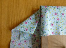 A photo showing Step 3, folding over the corner to make a triangle