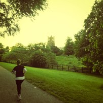 A photo of Emma running up Cherry Hill with a view of the Cathedral to the right.