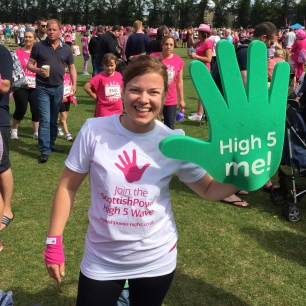 """A photograph of Emma holding the giant green hand from the Scottish Power """"High 5 Wave"""" campaign."""
