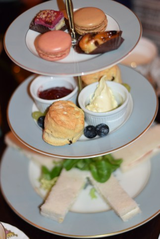 A photograph of a lovely spread of cut sandwiches, scones and bitesize cakes