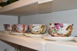 A photograph of four teacups and saucers on a shelf.