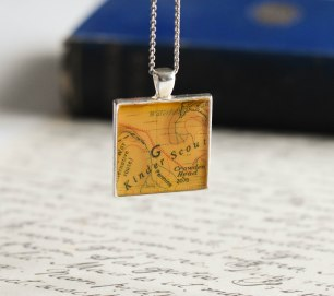 A photograph of the Kinder Scout pendant hanging over a handwritten letter with Robinson Crusoe book in the background