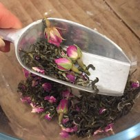 A photograph of a small scoop of Green Monkey, rose buds and vanilla