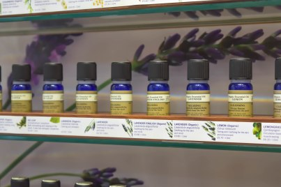 A photograph of a line of small bottles containing essential oil blends