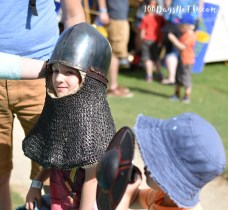 A photograph of Ollie trying some replica chain mail and helmet.
