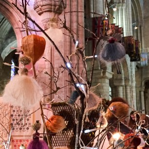 A photograph of some really delicate, handmade fairies hanging on some large twigs with fairy lights