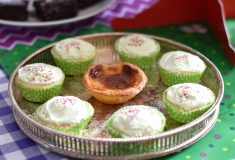 A photograph of seven cupcakes with green icing and in the centre is a pastie de nata