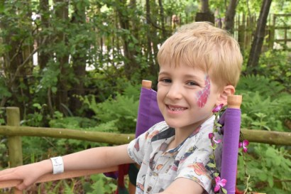 A photograph of Ollie sitting in the face paint chair looking very happy.