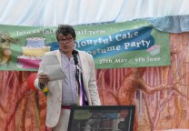 A photograph of Tom Blofeld reading a poem at the press event.