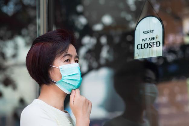 Pessoa com máscara em frente ao comércio fechado