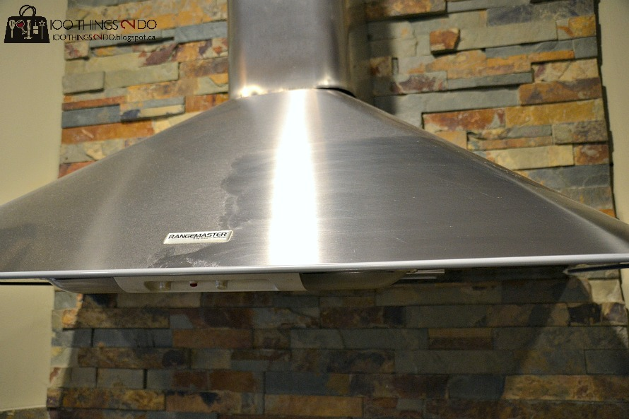 stainless steel free-standing range hood covered in dust and grease