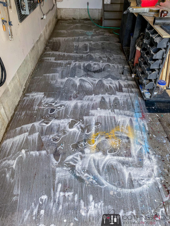 scrubbing the garage floor with Rust-Oleum cleaner & degreaser