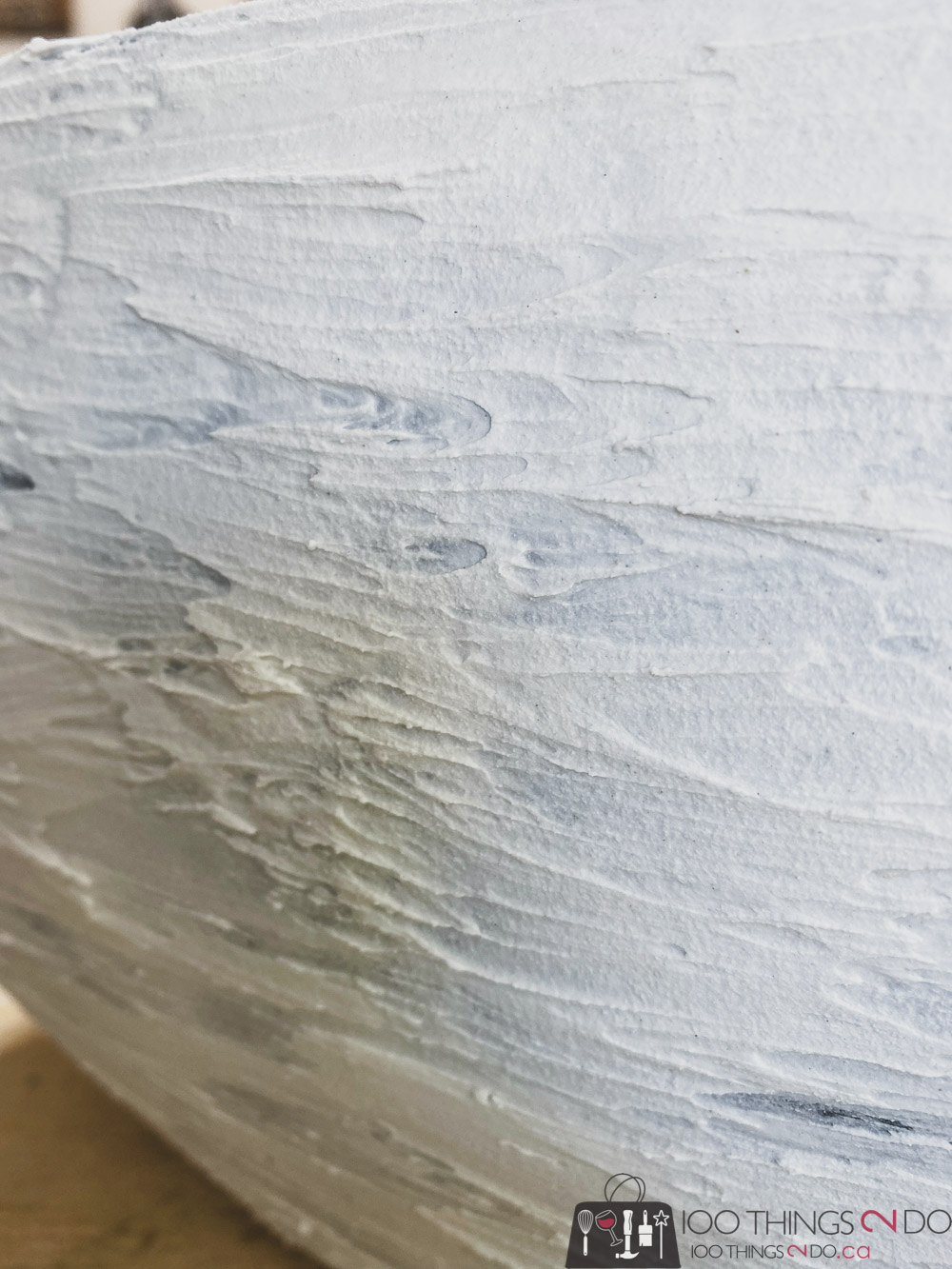 applying drywall putty to a planter