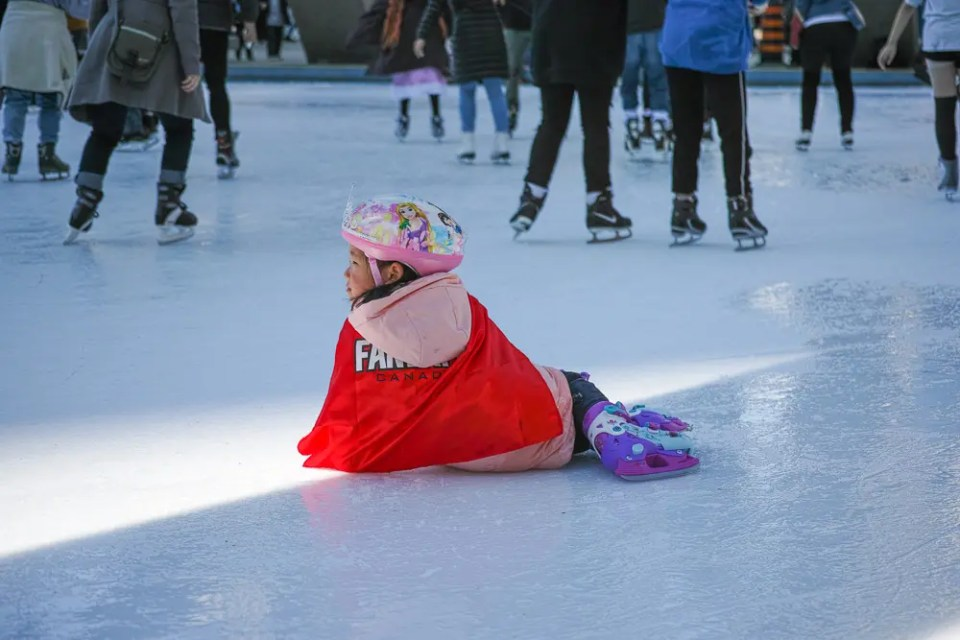 Small girl skater laying on the ice ring