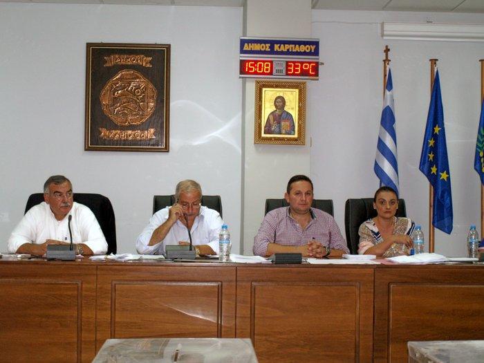 από αριστερά είναι ο Δήμαρχος Καρπάθου κ. Λάμπρος, στη συνέχεια ο Πρ. του Δημοτικού Συμβουλίου  κ. Γεώργιος Τούμας, ο Αντιπρόεδρος  Δ. Σ. κ. Νικόλαος Σπανός, και η γραμματέας του Δ. Σ.  Σοφία Σακέλλη