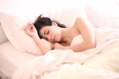 woman sleeping on white sheets