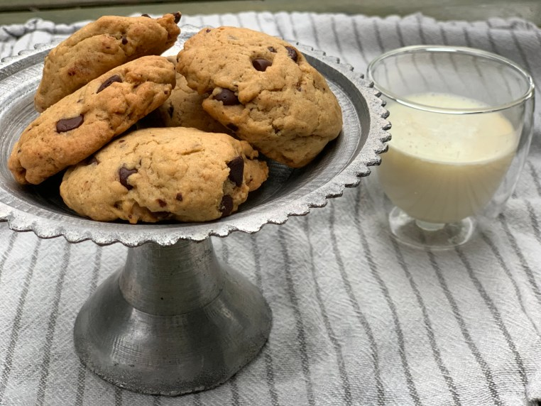A silver plate of chocolate chip cookies and milk on a cloth napkin