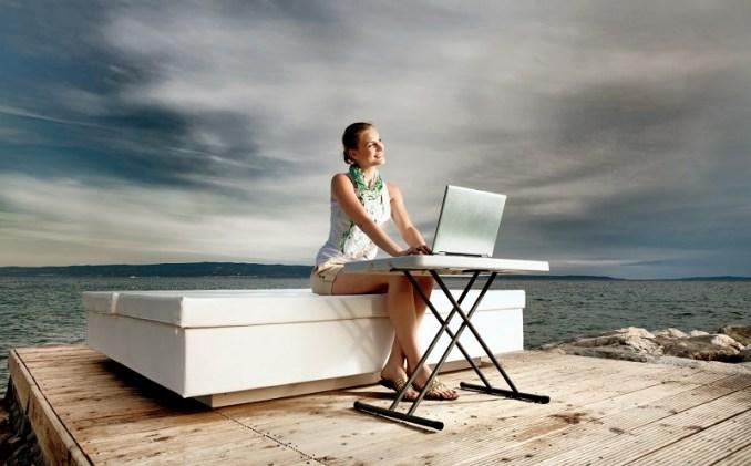 Jeune femme au bord de la mer, en train de travailler pendant son congé sabbatique