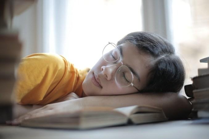 Femme faisant la sieste la tête sur un livre