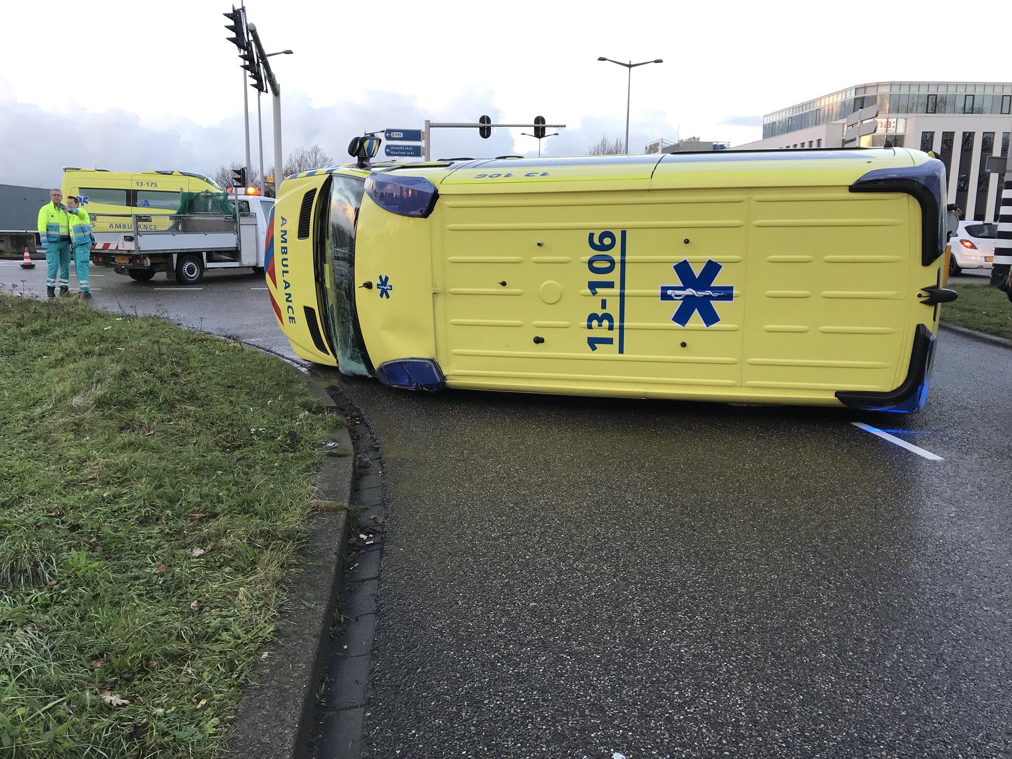 Ambulance op zijn zijkant geraakt na een aanrijding met een auto.