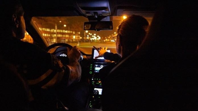 Zicht vanaf de achterbank van een politie-auto ('s nachts)