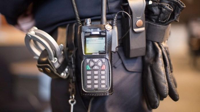 Agent draagt op de heup een portofoon, handboeien, pepperspray en handschoenen